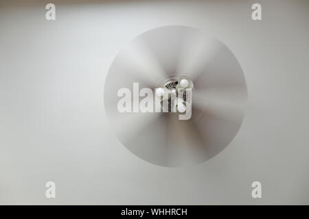 Ceiling fan with a ceiling lamp turned on, working with blurred blades in a living room - Stock Photo