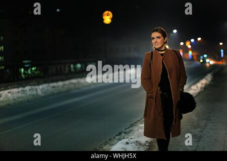 Young Woman On City Street At Night - Stock Photo
