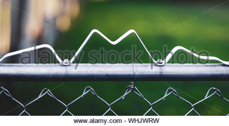 Selective focus closeup of the top railing of a chain link fence with metal in the shape of the letter m bolted on top. - Stock Photo