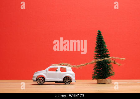 Close-up Of Christmas Tree By Toy Car On Table Against Red Background - Stock Photo