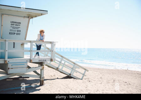 Mid Adult Woman Standing On Lifeguard Hut At Beach Against Clear Sky - Stock Photo