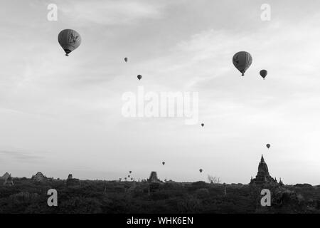 BAGAN, MYANMAR - 06 DECEMBER, 2018: Black and white picture of hot air balloons over the old temples in Bagan, Myanmar - Stock Photo