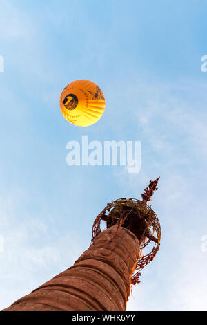 BAGAN, MYANMAR - 06 DECEMBER, 2018: Vertical picture from bottom to top of hot air balloon and an orange buddhist stupa in Bagan, Myanmar - Stock Photo
