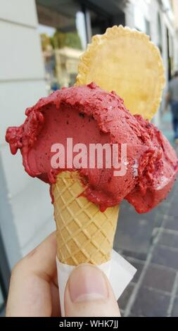 Close-up Of Hand Holding Ice Cream Cone - Stock Photo