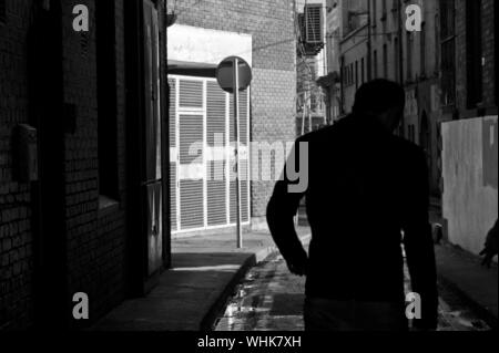 Rear View Of A Man Walking Down Alley - Stock Photo