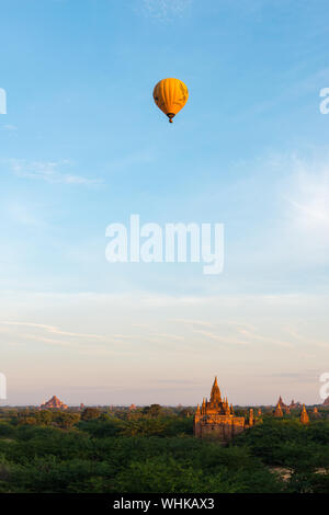 BAGAN, MYANMAR - 06 DECEMBER, 2018: Vertical picture of hot air balloon over the old temples during sunny day in Bagan, Myanmar - Stock Photo