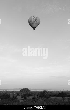 BAGAN, MYANMAR - 06 DECEMBER, 2018: Black and white picture of hot air balloon flying over the old temples in Bagan, Myanmar - Stock Photo