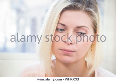 Close-up Of Thoughtful Young Woman Wearing Nose Ring - Stock Photo