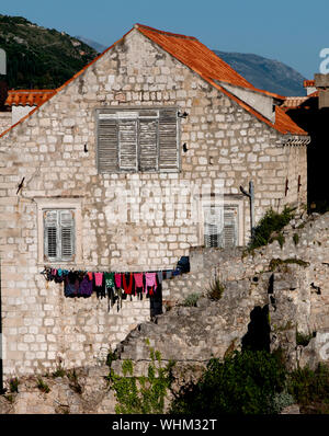An original home in Old Town, Dubrovnik, Croatia. Wash hangs out of the windows on this house on a steep path. - Stock Photo