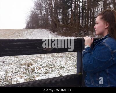 Woman Standing By Wooden Fence On Field During Winter - Stock Photo