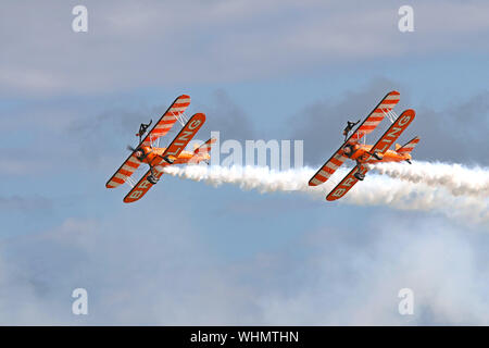 The Breitling Wingwalkers with their 1940's biplanes and the young ladies strapped on top wows the crowd at Eastbourne's International Airshow, 2017. - Stock Photo