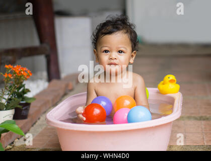 Portrait Of Shirtless Baby Boy Playing With Colorful Balls In Bathtub - Stock Photo