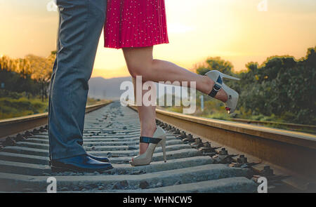 Low Section Of Couple Standing On Railroad Track - Stock Photo
