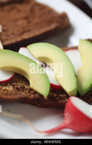 High Angle View Of Avocado And Radish Slices On Brown Bread - Stock Photo