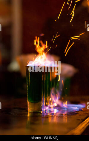 Close-up Of Burning Cocktail In Glass On Bar Counter - Stock Photo