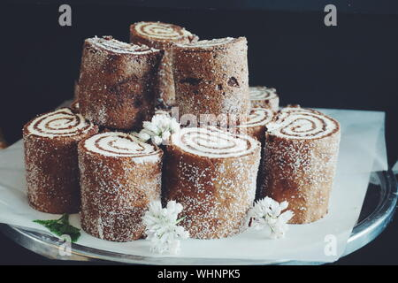 Swiss Rolls Decorated With Flowers In Plate Against Black Background - Stock Photo