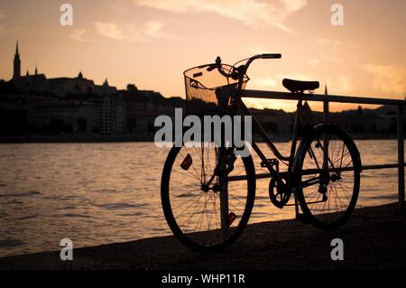 Bicycle Parked On Footpath By Danube River Against Sky During Sunset - Stock Photo