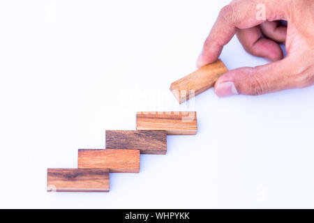 Cropped Hand Of Man Arranging Toy Blocks Over White Background - Stock Photo