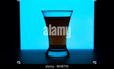 Glass or stemware with alcohol wine,whiskey,gin,beer,rum,vodka,Scotch,cognac,liquor,brandy,absinthe or cocktail on a blue background. A glass on the b - Stock Photo