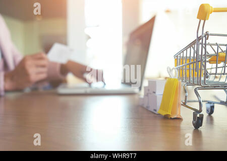 Cropped Hands Of Man Making Card Payment Over Laptop On Table - Stock Photo