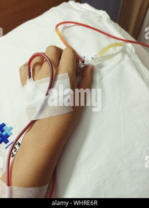 Cropped Hand With Iv Drip On Bed In Hospital - Stock Photo
