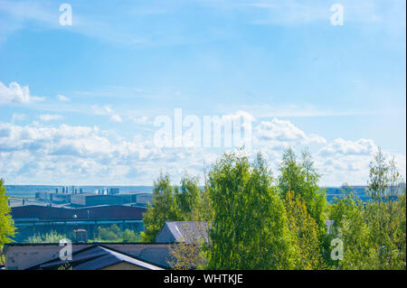 Summer industrial landscape - the roofs of industrial buildings against the blue sky with white clouds, in the background - the river