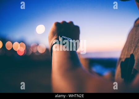 Cropped Image Of Man Hand Wearing Smart Watch Against Sky During Sunset - Stock Photo