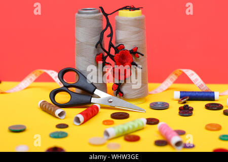Two large spools of thread are standing, many small spools are lying. Large scissors for sewing, but the photo has buttons and a measuring tape. Needl - Stock Photo
