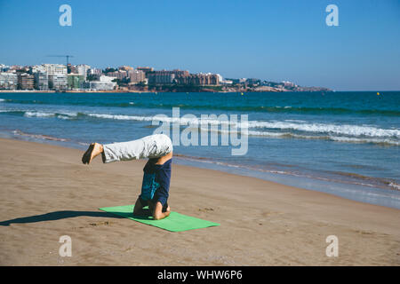 Full Length Of Man Performing Handstand While Doing Yoga At Beach Against Clear Blue Sky - Stock Photo