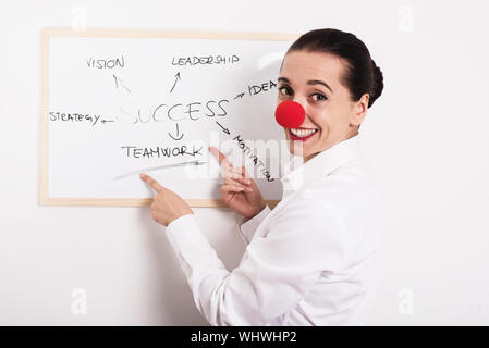 Portrait Of Smiling Businesswoman Wearing Clown Nose While Pointing On Whiteboard At Office - Stock Photo