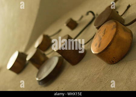 Low Angle View Of Old Kitchen Utensils Hanging On Wall - Stock Photo