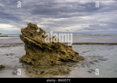 Beautiful eroded rock at low tide on ocean coastline. Stormy weather and low tide - Stock Photo