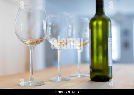 Three clear wine glasses and a bottle of chilled white wine on a wooden table - Stock Photo