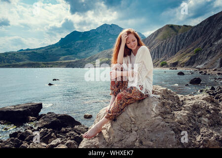 Beautiful boho styled model wearing white crochet swimsuit posing on the beach in sunlight. Red-haired girl with freckles. Crimea, Fox bay, Koktebel - Stock Photo