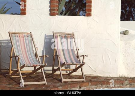Deck Chairs On Footpath Against Wall