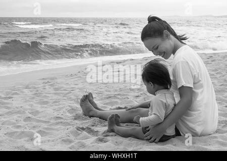 Mother and her child playing on the beach together outdoors - Stock Photo