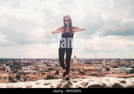 Young Woman Standing On Retaining Wall At Vilnius Old Town Against Sky - Stock Photo