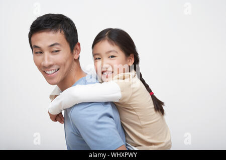 Side view of a young girl getting piggyback ride with father - Stock Photo