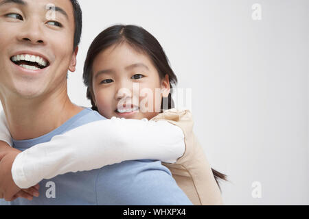 Closeup of a young girl getting piggyback ride with father - Stock Photo