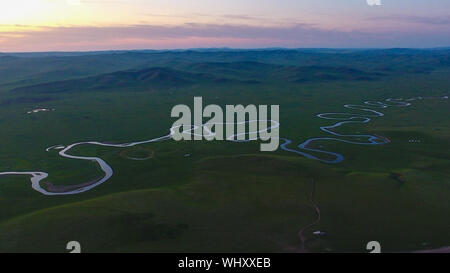 (190903) -- BEIJING, Sept. 3, 2019 (Xinhua) -- Aerial photo taken on Aug. 29, 2019 shows the Morigele River at sunset in Hulun Buir, north China's Inner Mongolia Autonomous Region. China has adopted the vision that lucid waters and lush mountains are invaluable assets and pursued a holistic approach to conserving its mountains, rivers, forests, farmlands, lakes, and grasslands. At the very highest levels, China is driving the way forward in the construction of an ecological civilization. (Xinhua/Peng Yuan) - Stock Photo