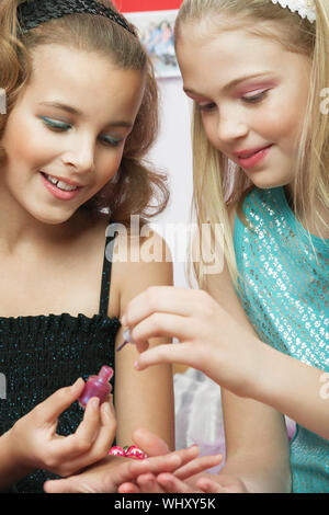 Closeup of a young girl applying nail polish to friend's fingernails - Stock Photo