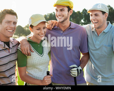 Cheerful young golfers with arms around on golf course - Stock Photo