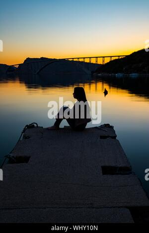 Solitude and loneliness teen girl silhouetting profile against horizon bridge in distance background contour for mental health - Stock Photo
