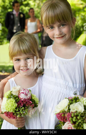 Portrait of cute little bridesmaids holding bouquets in garden - Stock Photo