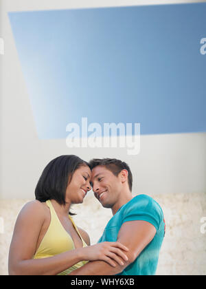 Low angle view of an affectionate young couple under skylight - Stock Photo