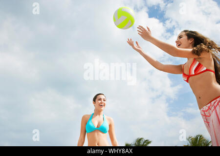 Happy teenage girls playing beach volleyball against cloudy sky - Stock Photo