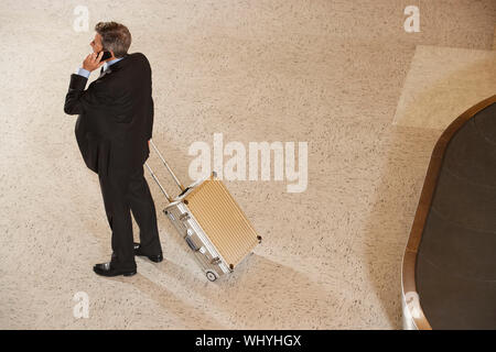 Elevated full length view of a businessman with suitcase using cellphone by luggage carousel in airport - Stock Photo