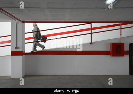 Side view of a businessman walking down ramp in parking garage with luggage - Stock Photo
