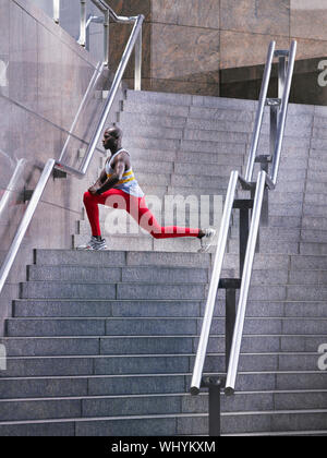 Side view of an African American man stretching on staircase outside building - Stock Photo