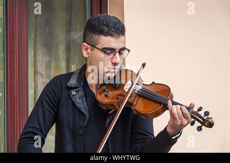 Dnipro, Ukraine - September 29, 2018: Young guy violinist rehearses on violin before entering the street scene - Stock Photo